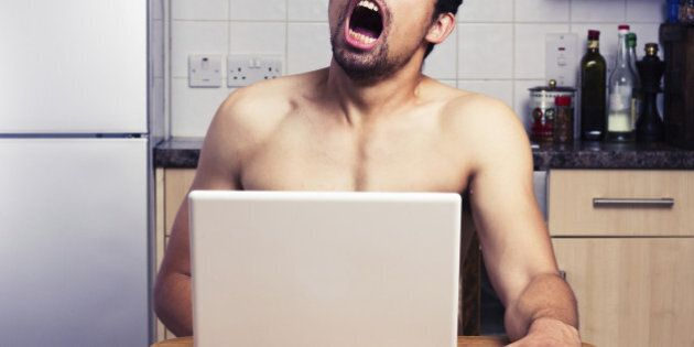 Young naked man is watching pornography on a laptop in his kitchen and masturbating