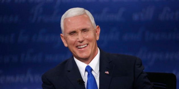 Republican U.S. vice presidential nominee Governor Mike Pence laughs as he discusses an issue with Democratic...