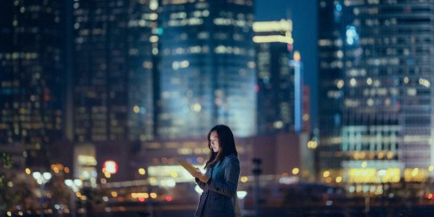 Pretty office lady is using digital tablet, standing against illuminated highrise corporate buildings at night time.