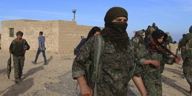 Des combattants des Forces démocratiques syriennes transportent leurs armes dans le village de Ghazila...