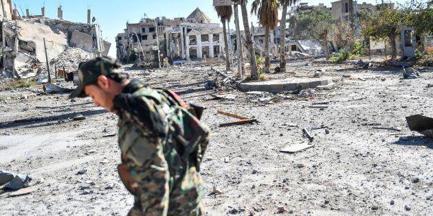 Un membre des Forces démocratiques syriennes arpente les rues désertes de