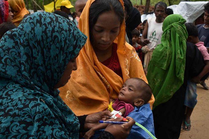 Une nutritionniste mesure la circonférence du bras du jeune Anamul, âgé de neuf mois.