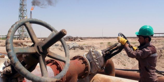 A worker checks the valve of an oil pipe at Al-Sheiba oil refinery in the southern Iraq city of Basra,...