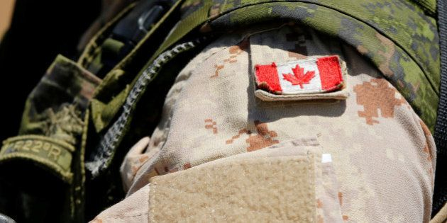 A Canadian soldier from the Royal 22nd Regiment wears a Maple Leaf flag on his uniform during a non-combative...