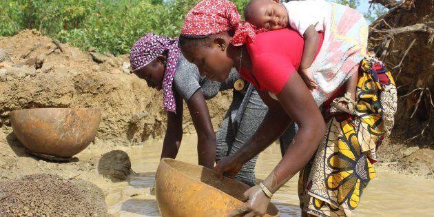Daby dort sur le dos de sa mère pendant que celle-ci drague la rivière à la recherche d'or dans l'ouest du Mali.