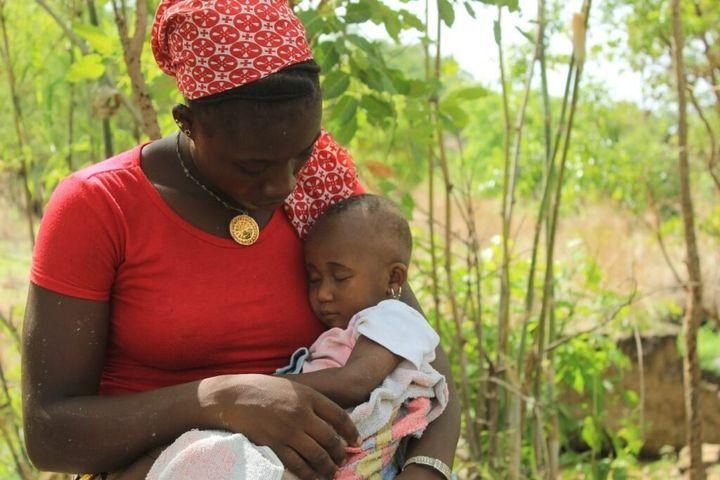 Cira avec sa fille, Daby, dans ses bras. La jeune fille a été donnée en mariage à 14 ans à un homme qui a quitté le Mali pour trouver du travail.