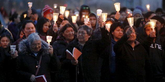 Des gens marchent lors d'une vigile à la chandelle, à Attawapiskat, en Ontario, le 15 avril