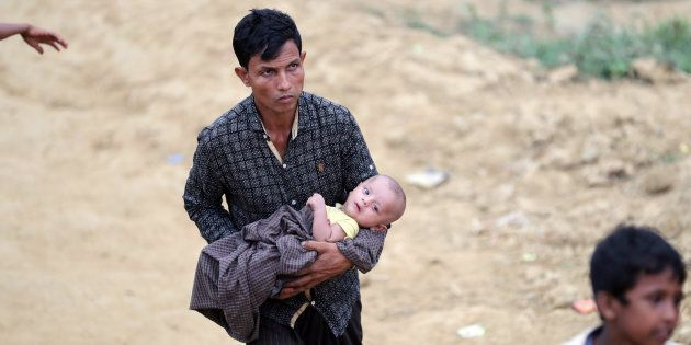 Un réfugié rohingya porte un enfant dans le camp de Palong Khali, à Cox's Bazar, au Bangladesh, le 17...