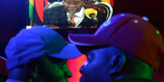 Des Zimbabwéens regardent la déclaration de Robert Mugabe à la télévision d'État dans un bar de Harare,...