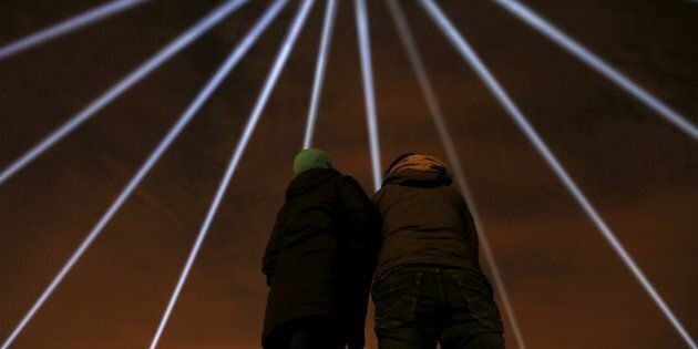 Des faisceaux lumineux éclairant le ciel de Montréal lors des commémorations de