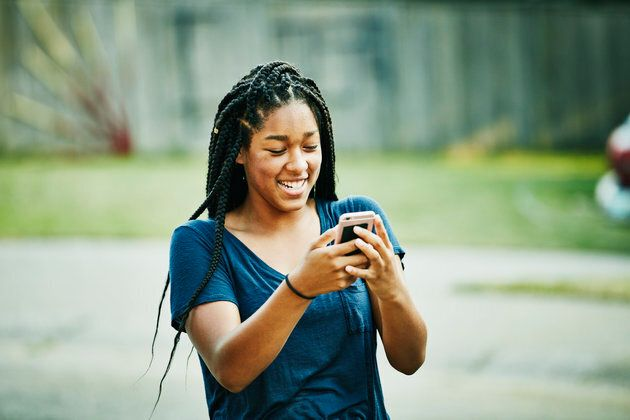 Laughing young woman looking at smartphone on summer