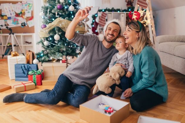 Photo of a cheerful young family, posing for a selfie during Christmas holiday