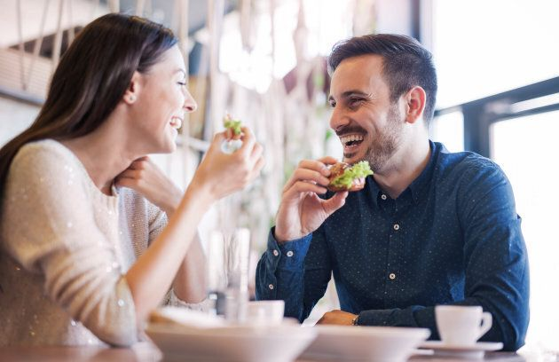 Happy loving couple enjoying breakfast in a cafe. Love, dating, food,
