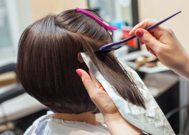 The hairdresser paints the woman's hair in a dark color, apply the paint to her hair in the beauty