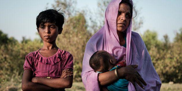 Mariom Khatun, réfugiée rohingya âgée de 25 ans, tient dans ses bras son bébé, Firuz Ahmed, âgé de 5 mois, alors qu'ils se reposent sur les rives de la rivière Naf, dans le district de Cox's Bazar, au Bangladesh, après un périple de six heures pour traverser la rivière sur une embarcation de fortune.