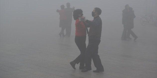 Des danseurs portent un masque dans un smog épais à Fuyang, en