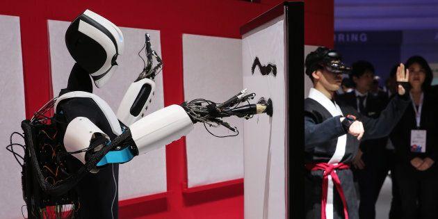 Un robot, contrôlé par un humain, peint.