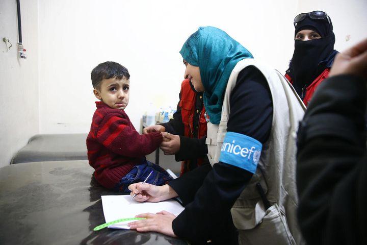 Le 15 mars 2018, une spécialiste de la nutrition de l'UNICEF vérifie l'état de santé des enfants dans une clinique de santé à Douma, en Ghouta orientale, Syrie.