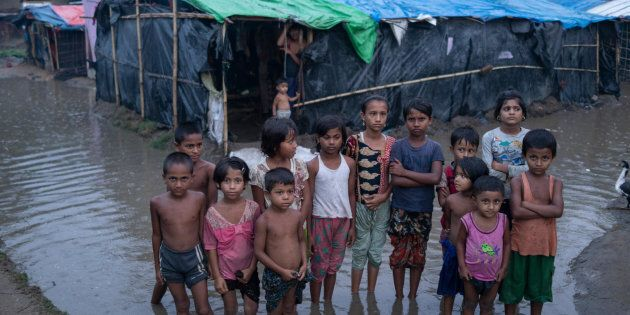 Des enfants rohingyas marchent péniblement dans l'eau, alors que les pluies ont encerclé leurs abris de fortune, suite à des pluies intenses. District de Cox's Bazar, Bangladesh, 20 mai 2018.