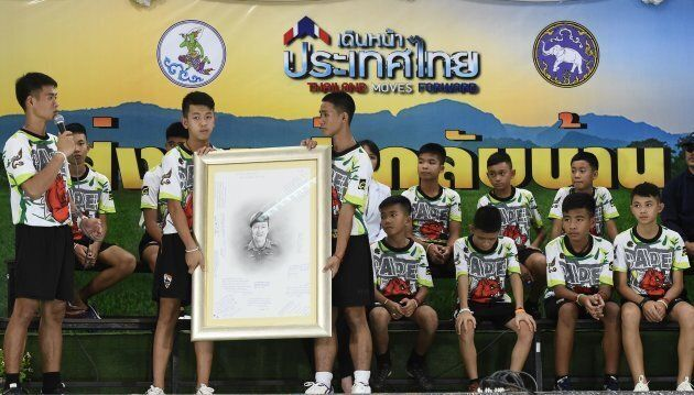 Les 12 joueurs de soccer et leur entraîneur ont rendu hommage au plongeur qui est décédé en tentant de...