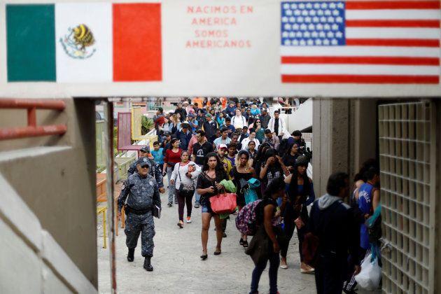 Des membres d'une caravane de migrants en provenance d'Amérique centrale arrivent à la frontière entre...