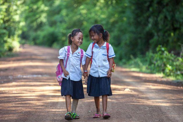 Channa (7 ans), amputée, marche avec une camarade de classe sur le chemin de l'école au Cambodge