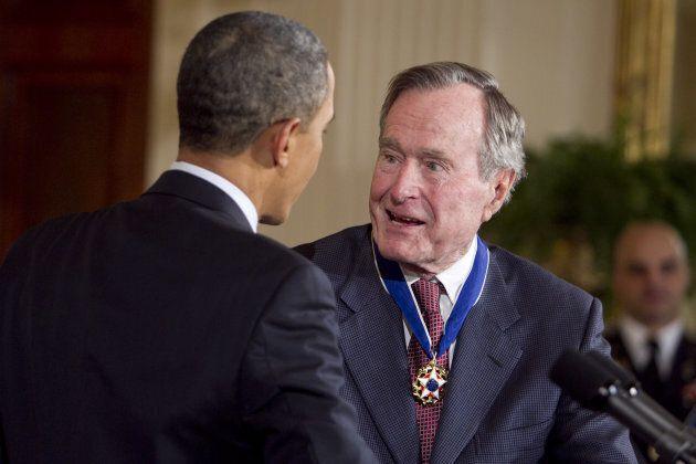 L'ex-président George H.W. Bush alors qu'il recevait la Médaille de la Liberté, discutant avec le président...