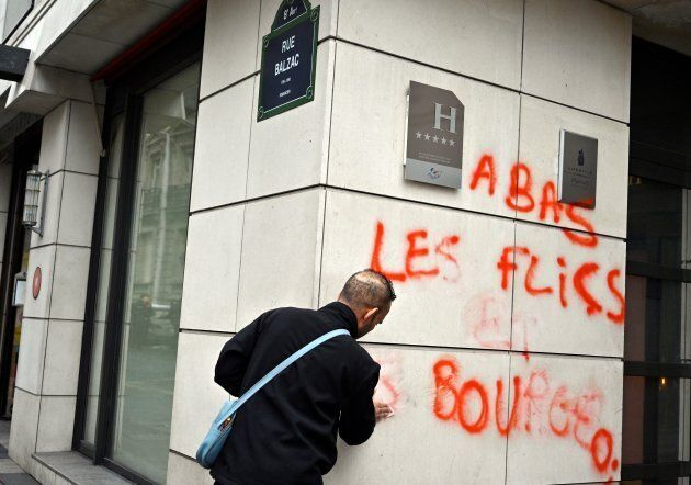 Un travailleur s'affaire à effacer les graffitis sur un hôtel de Paris,