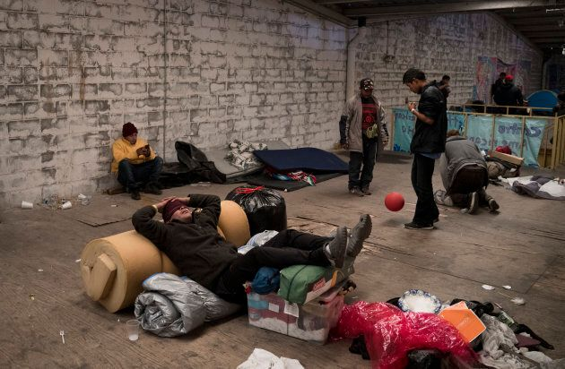 Un homme originaire du Honduras se repose sur ses effets personnels dans un entrepôt devenu un refuge...