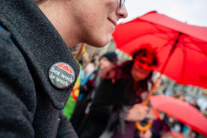 Une participante à la marche internationale de la journée des femmes porte un macaron indiquant que le travail du sexe est un travail.