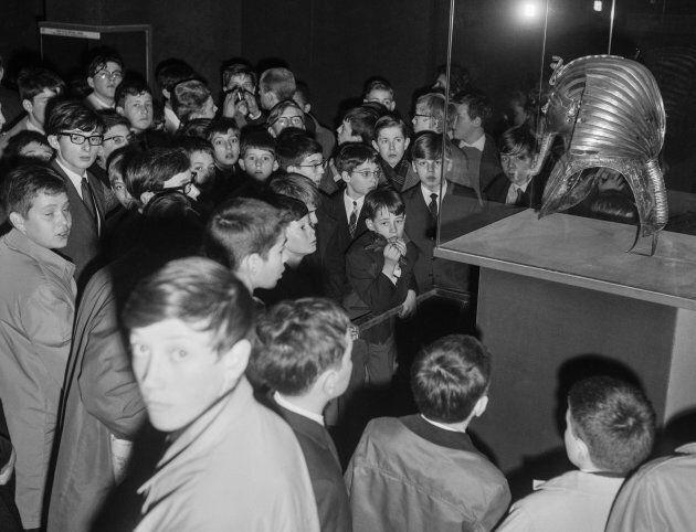 Groupe de jeunes devant le masque funéraire du pharaon Toutankhamon lors de l'exposition «Toutankhamon et son temps» au musée du Petit Palais à Paris en France, le 23 mars 1967.