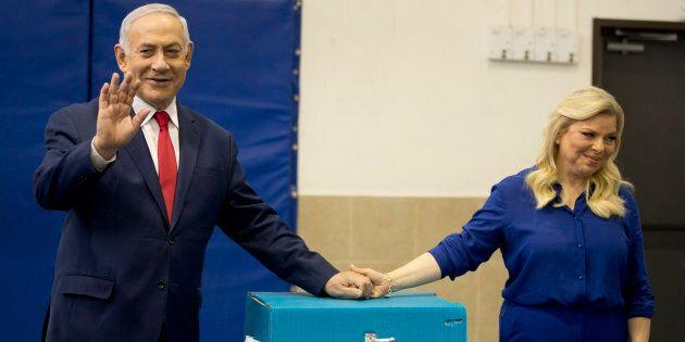 Le premier ministre israélien Benjamin Netanyahu, à gauche, fait des vagues avec sa femme Sara après avoir voté lors des élections législatives israéliennes à Jérusalem, le mardi 9 avril 2019.