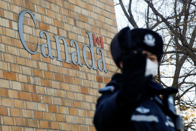 Un policier ne semble pas apprécier qu'un photographe prenne des photos devant l'ambassade du Canada...