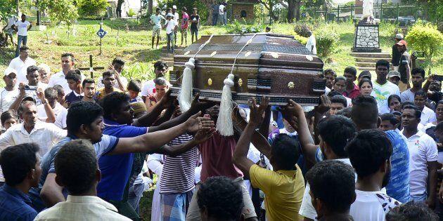 Des proches d'une des nombreuses victimes des attentats transportent un cercueil dans un cimetière de...