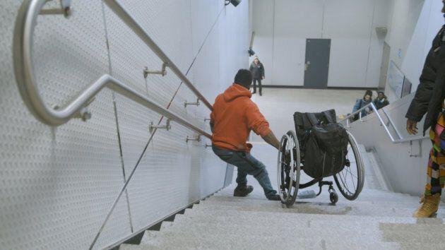 Woddy Belfort descend les marches avec son fauteuil roulant à la station