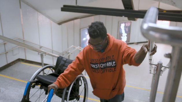 Woody Belfort escalade les marches avec son fauteuil roulant à la station Berri-UQÀM.
