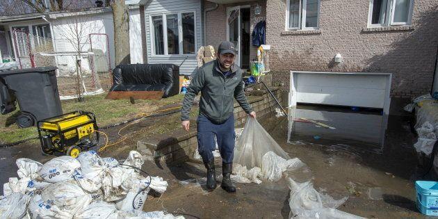 Un résident de Sainte-Marthe-sur-le-Lac ramasse des débris devant sa demeure, mardi