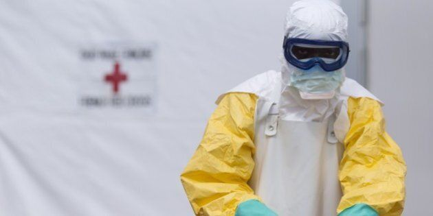 A health worker wearing a personal protective equipment (PPE) works at the Ebola treatment center run...