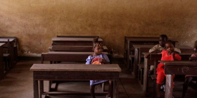 School children sit inside their class room a they await the arrival of their teacher in the city of...