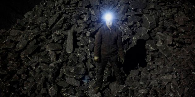 SHANXI, CHINA -NOVEMBER 25: (CHINA, HONG KONG, MACAU, TAIWAN OUT) A Chinese mine worker wears a headlamp as he stands in a pile of coal at a mine on November 25, 2015 in Shanxi, China. A history of heavy dependence on burning coal for energy has made China the source of nearly a third of the world's total carbon dioxide (CO2) emissions, the toxic pollutants widely cited by scientists and environmentalists as the primary cause of global warming. China's government has publicly set 2030 as a deadline to reach the country's emissions peak, and data suggest the country's coal consumption is already in decline.  (Photo by Kevin Frayer/Getty Images)