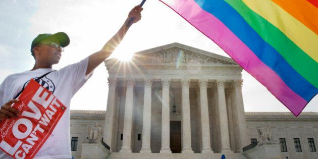 Carlos McKnight of Washington, waves a flag in support of gay marriage outside of the Supreme Court in...