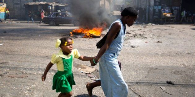 A woman and a child walk past a burning barricade during a protest against President Michel Martelly's...