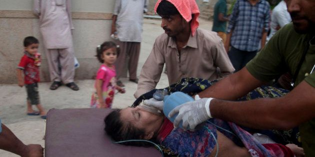 People rush a woman to a hospital as she suffered from a heatstroke in Karachi, Pakistan, Wednesday,...