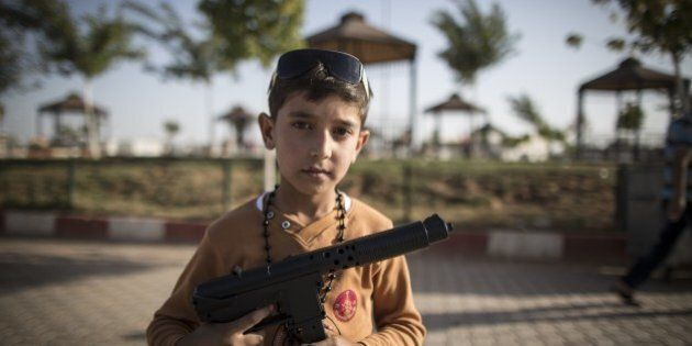 SANLIURFA, TURKEY - SEPTEMBER 24: A Syrian refugee boy poses with a toy gun at a tent city in the Akcakale...