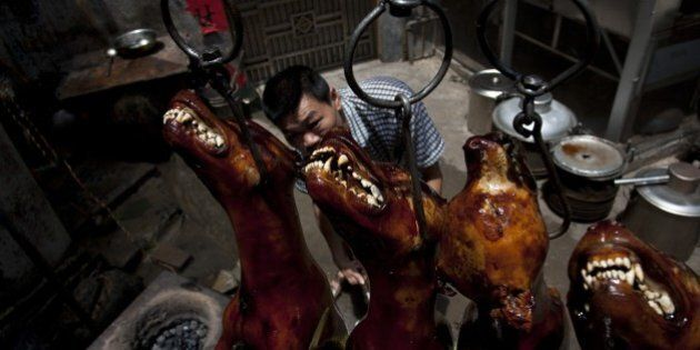 A Chinese vendor waits for customers as he hangs up cooked dogs at his stall in Yulin, in southern China's...