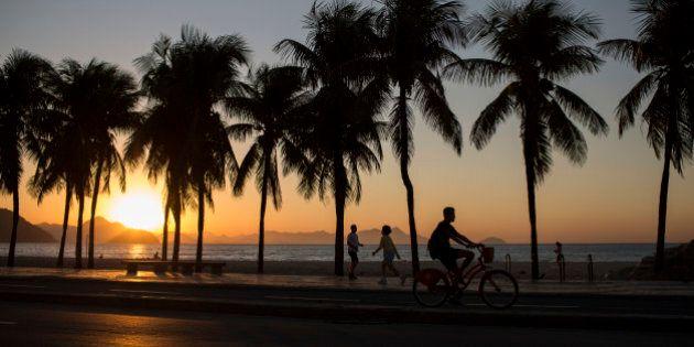 People exercise along Copacabana beach as the sun rises in Rio de Janeiro, Brazil, Wednesday, July 27,...