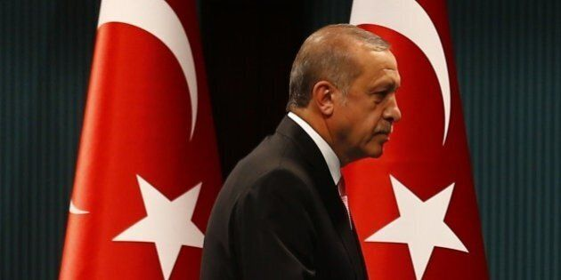 Turkish President Tayyip Erdogan leaves after a news conference following the National Security Council...