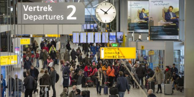 Passengers pull their luggage through a departure hall at Schiphol Airport, operated by the Schiphol...