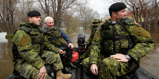 Canada's Governor General David Johnston (2-L) tours a flooded residential area with Major Manuel Pelletier-Bedard...