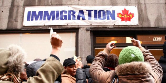 Members of Canada's Haitian community stand in line at an immigration consulting office in Montreal January...